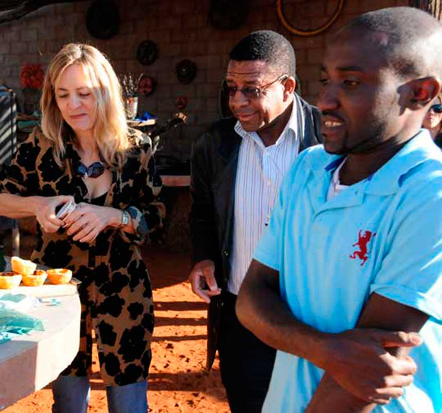 Eugenie Briedenhann serving early morning coffee to Pastor Uanguta and his son